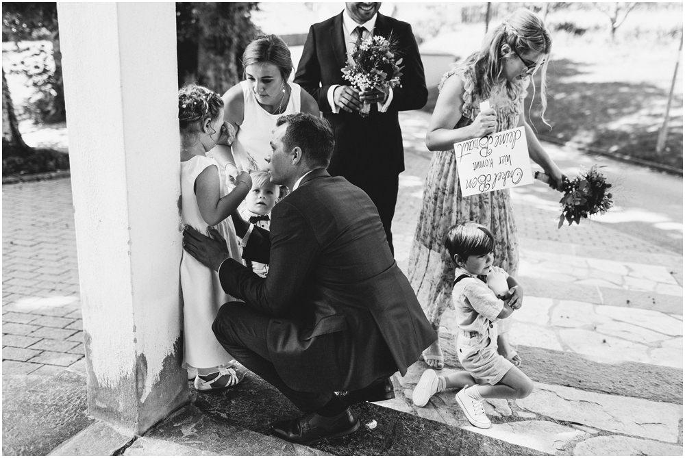 Braut und Bräutigam trösten ein Kind
