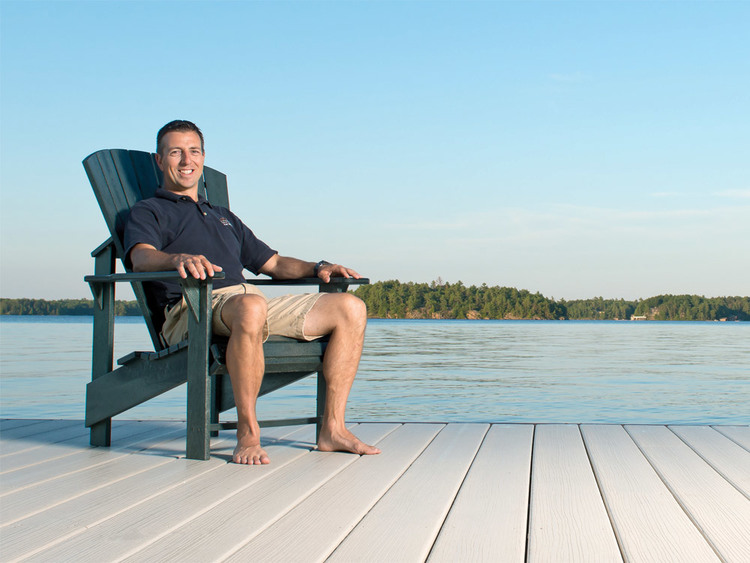 Jason soaking in the sunshine on a newly-installed Lumberock® dock on Lake Muskoka.