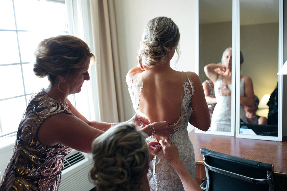 moms getting bride into her dress