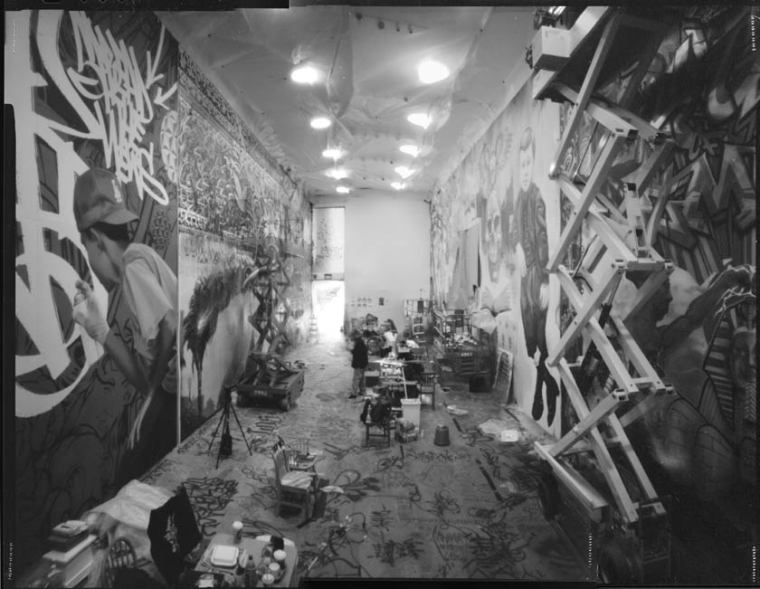 Stitched together, 3-panel, pinhole shot of the construction of the exhibition