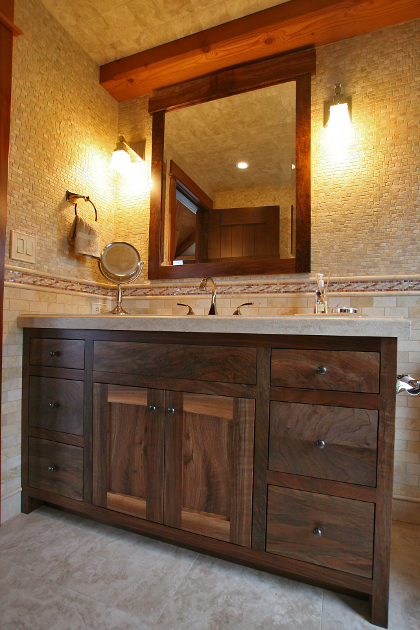 Claro Walnut was crafted into the vanity and mirror for this family bath. The stiles, rails and mirror frame feature live edges.