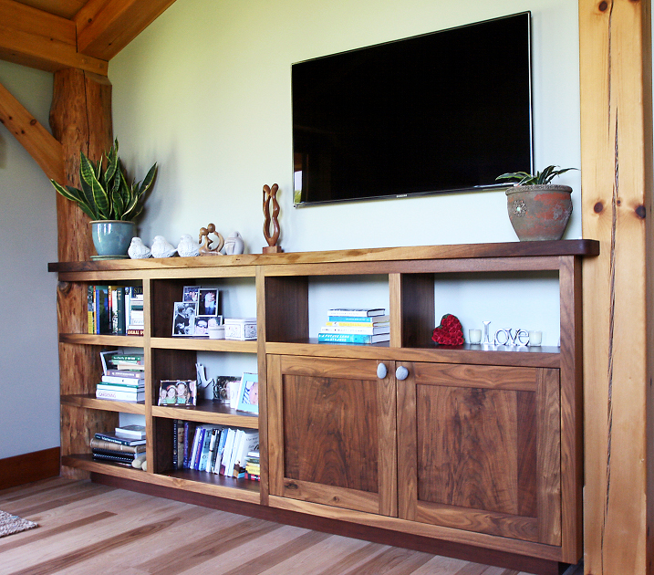 The open shelves of this walnut shelf system were hand scribed to fit the curve of the peeled oak post.