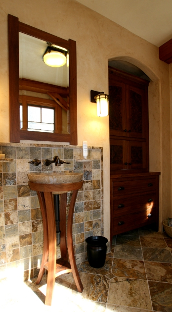 Custom walnut cabinetry joins a pedestal sink and walnut framed mirror to form a matching set.