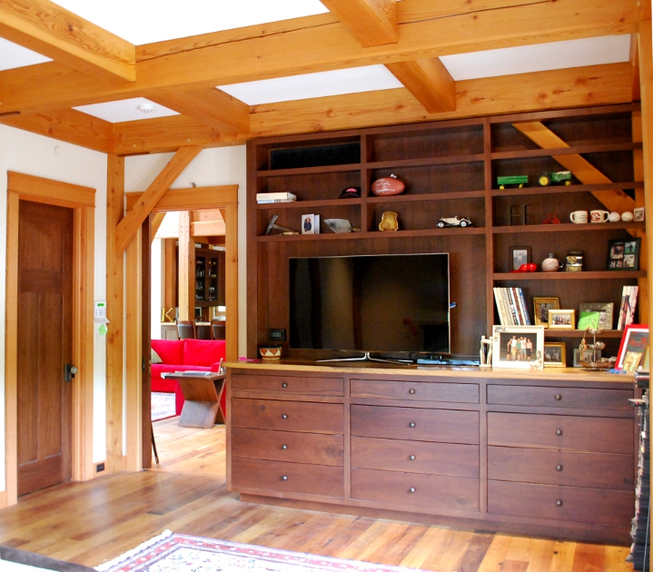 A custom walnut entertainment unit provides plenty of open and enclosed storage for a master bedroom. The open shelves wrap around the timber frame post and brace, celebrating the structure.