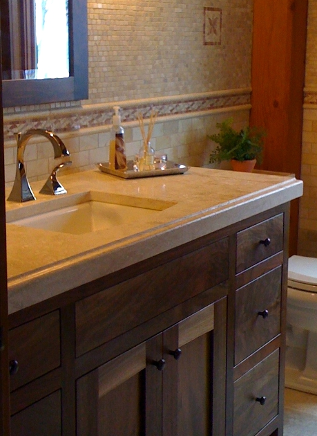 A limestone counter with inset sink tops a custom walnut vanity.