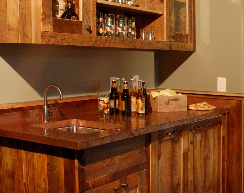 A hand-hammered copper top and sink are the perfect touch to this game room wet bar.