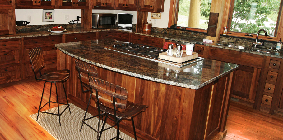 Granite tops bring additional color and character to a custom walnut kitchen.