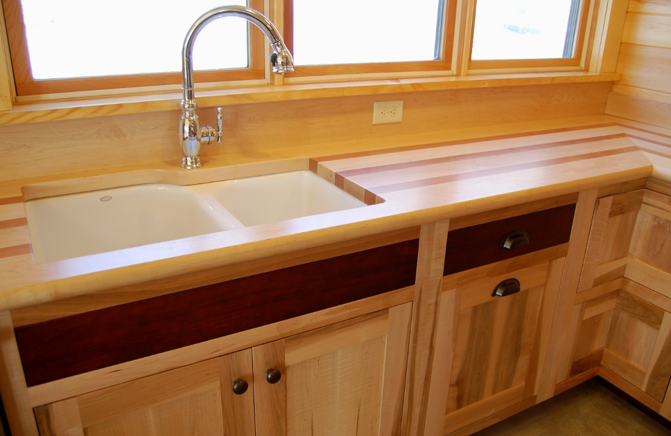 Custom maple cabinetry is topped with maple and cherry striped wood top.