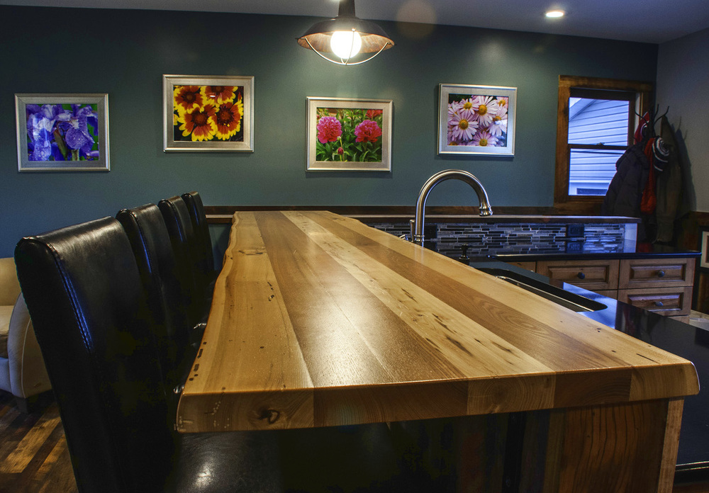 When Mary remodeled her kitchen in Buffalo NY she contacted us for a custom crafted live edge reclaimed Elm top to go with new-to-her reclaimed flooring and paneling.