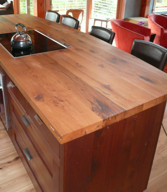 Reclaimed hardwood island counter on walnut cabinetry.