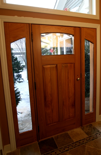 Updating the main entry for an existing home includes plenty of natural light through sidelights,a transom window and a smaller door window. D54