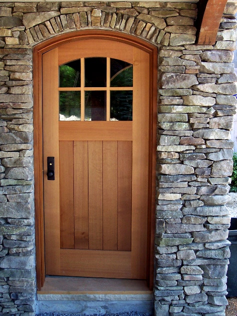 "This barn entry door features a curved top surrounded by hand fit field stone ""siding"". D37"
