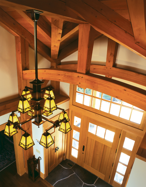 The curved transom of this Douglas fir door mimics the curved bottom chords of the trusses above while the sidelights allow a quick view of the golf course outside. D2