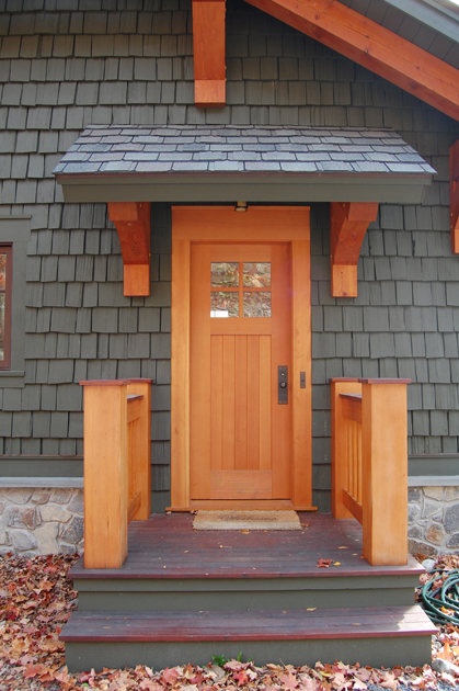 A small timbered overhang offers protection for the for Side doors for houses