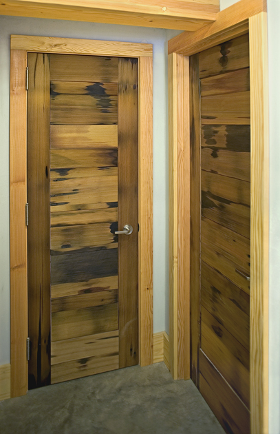 Reclaimed vat stock wood celebrates original patina on interior doors. D15