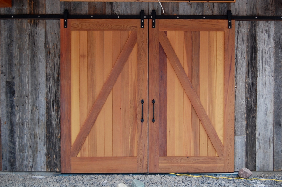 Western red cedar barn doors are surrouned by reclaimed barn siding giving this new barn the feel of having been on the land for decades. D41