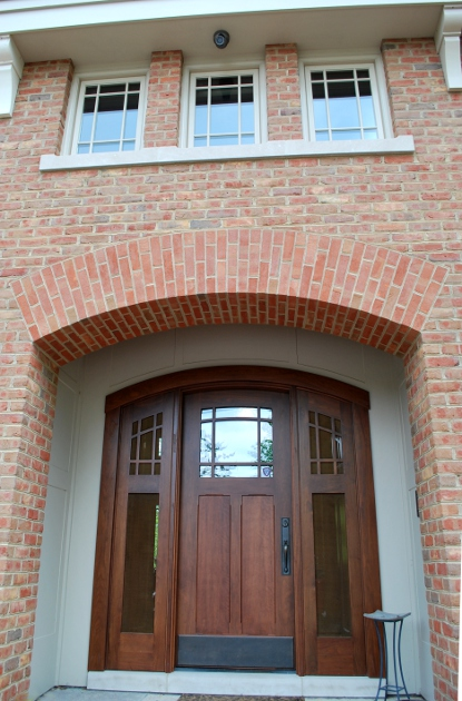 A curved walnut entry door is double the usual thickness to better fit screened and glass filled sidelights.
