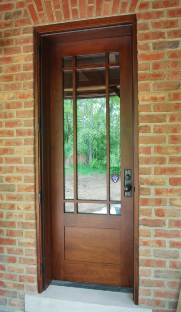 Custom walnut door allows access to the covered porch of a Kentucky timber frame home.