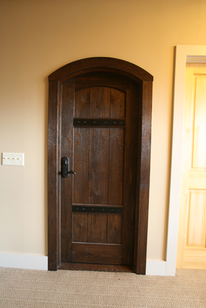 Custom stained oak with metal strapping makes a statment as the entry to the wine cellar in this upstate NY home.