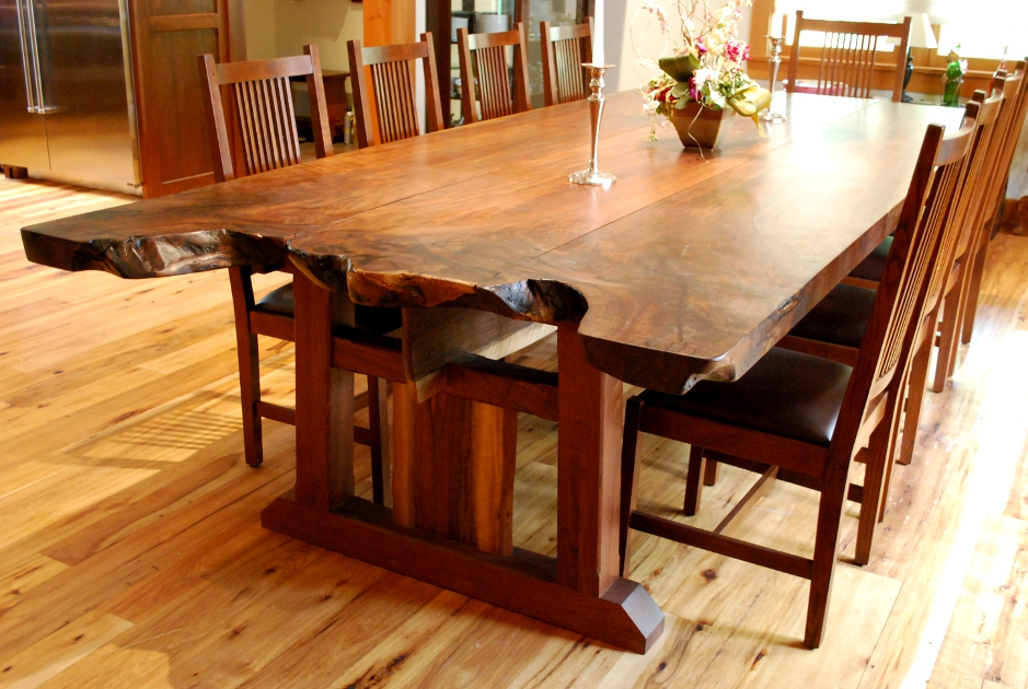 Slabs of claro walnut were crafted together maintaining live edges from the trunk and root area of the tree creating a very large family dining table.