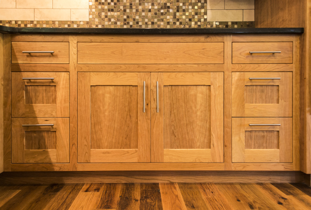 custom cherry cabinetry joins quartz and reclaimed oak countertops in the kitchen of tom and