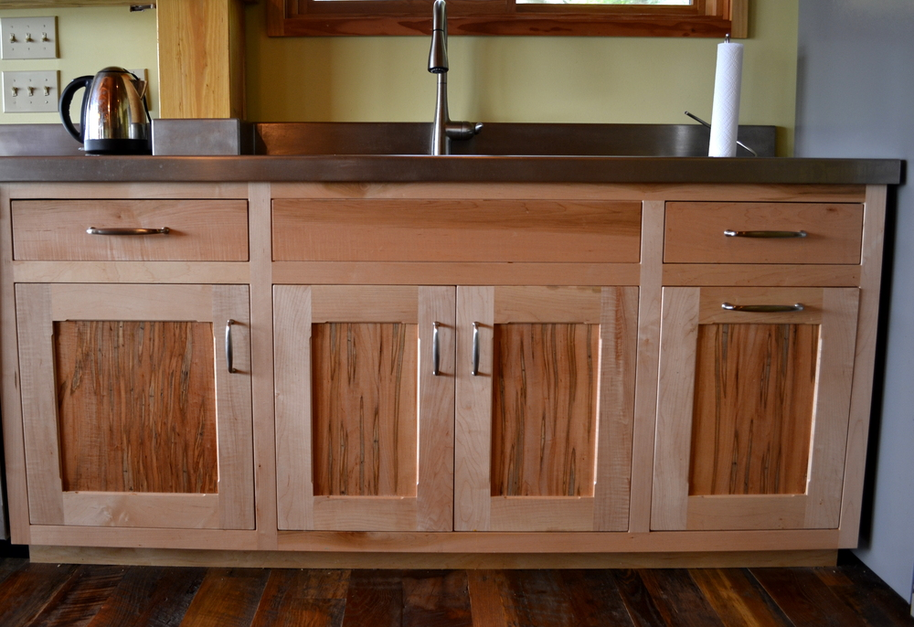 Maple surrounds frame Ambrosia Maple inset panels in a family kitchen.