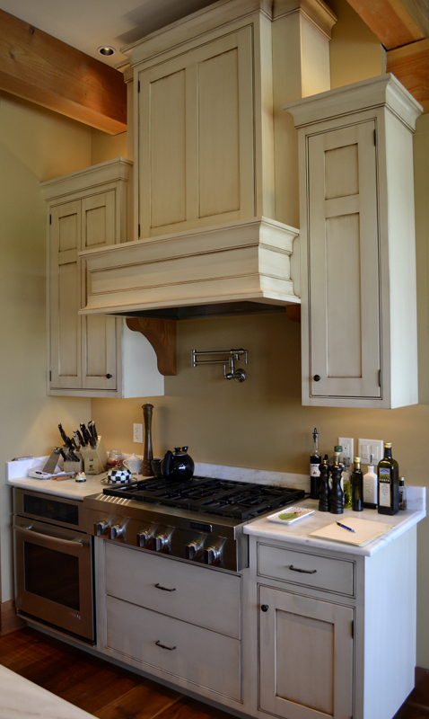 "The range hood surround was crafted to match the cabinetry (which sports a custom painted finish with ""worn"" edges) in a custom home."