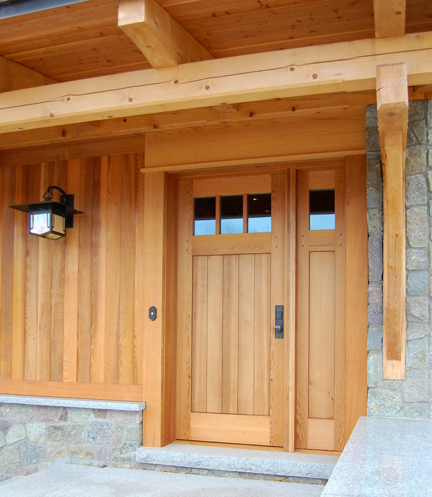 The design of a custom cedar door with a single sidelight mimics the exterior cedar paneling on a lake home. D20