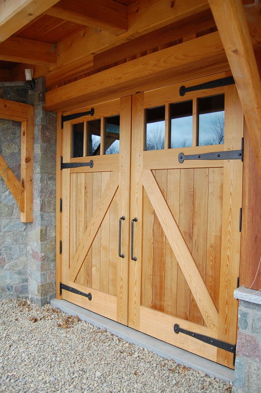 Looking more closely at the garage doors the strap hinges and heavy steel handles contrast against Western Red Cedar wood. D24