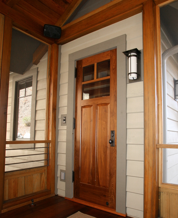 A custom walnut door leads to an enclosed porch on the back of a NC home.