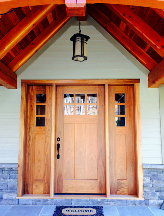 A custom walnut entry door with matching sidelights welcomes visitors to Ed and Tina's timber frame home in New York.
