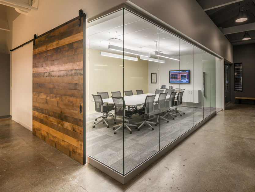 A reclaimed hardwood flat track conference room door adds warmth to the glass, steel, and concrete decor.
