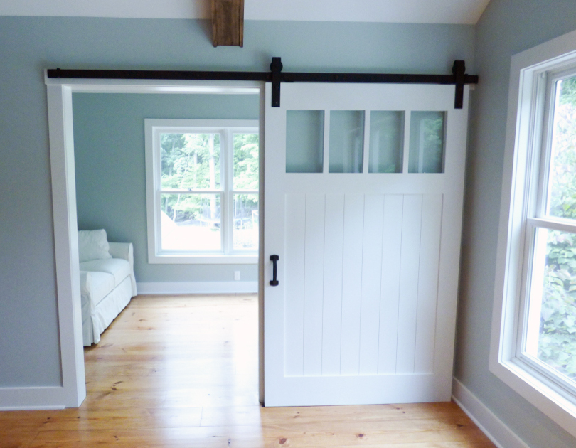 "Close to 50"" wide, this painted Flat Track Door from our fine woodworking group provides optional privacy for the sleeping quarters from the sitting room in a remodeled master suite."