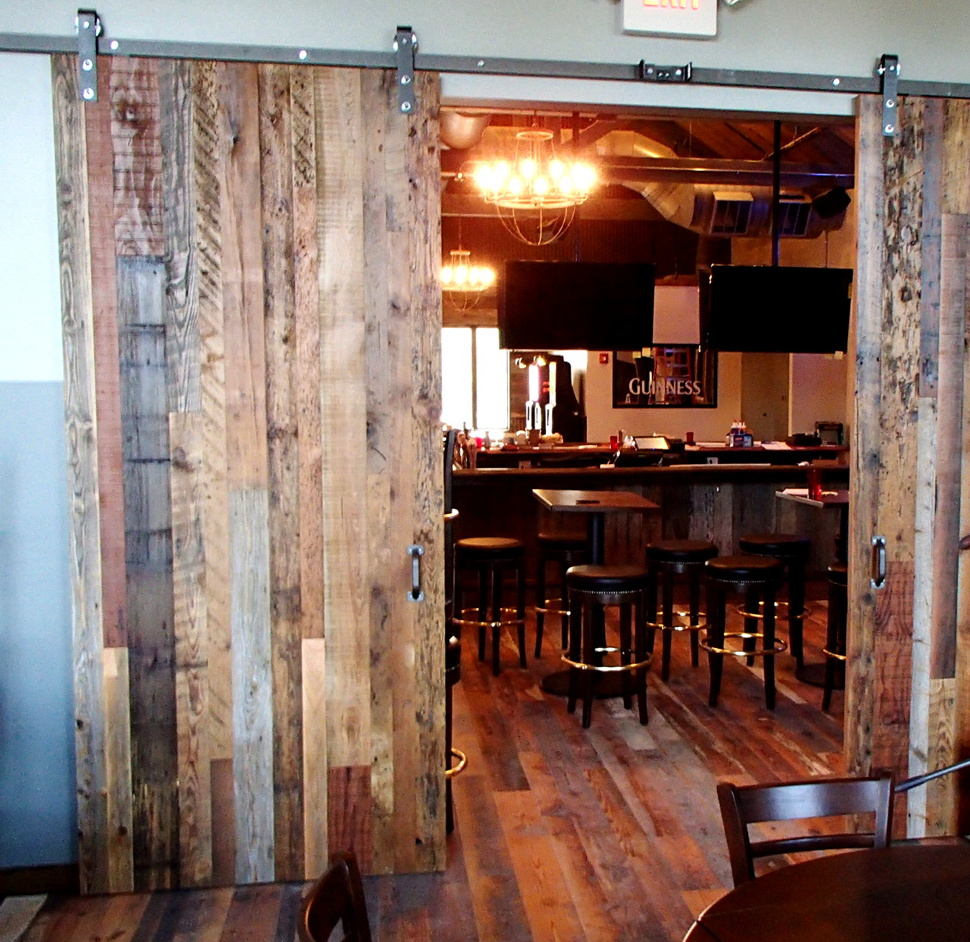 Jeremiah's Tavern features reclaimed mixed hardwoods flat track doors with steel toned hardware separating their banquet room from the main dining. (We recommend their wings!)