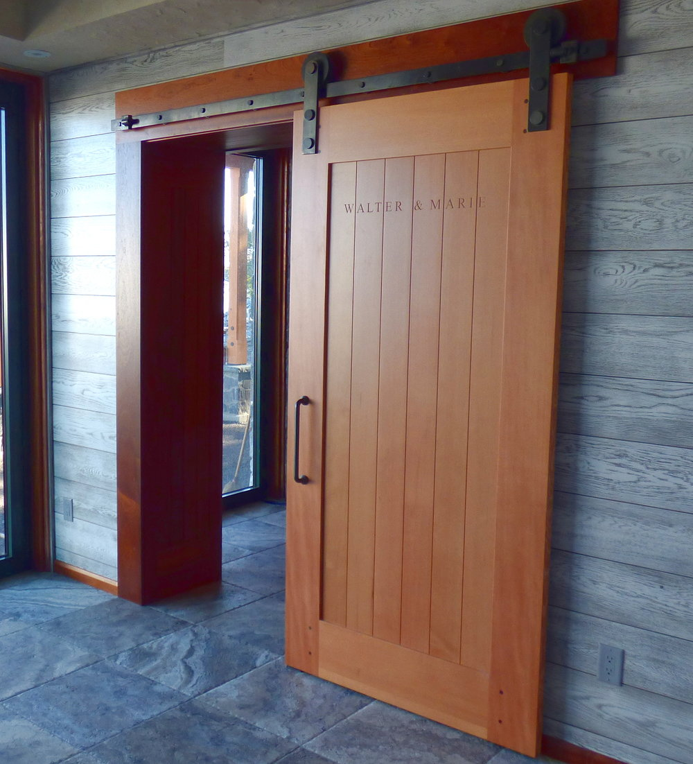 A clean grained Douglas fir flat track separates the exercise room and main entry of a timber frame guest house.