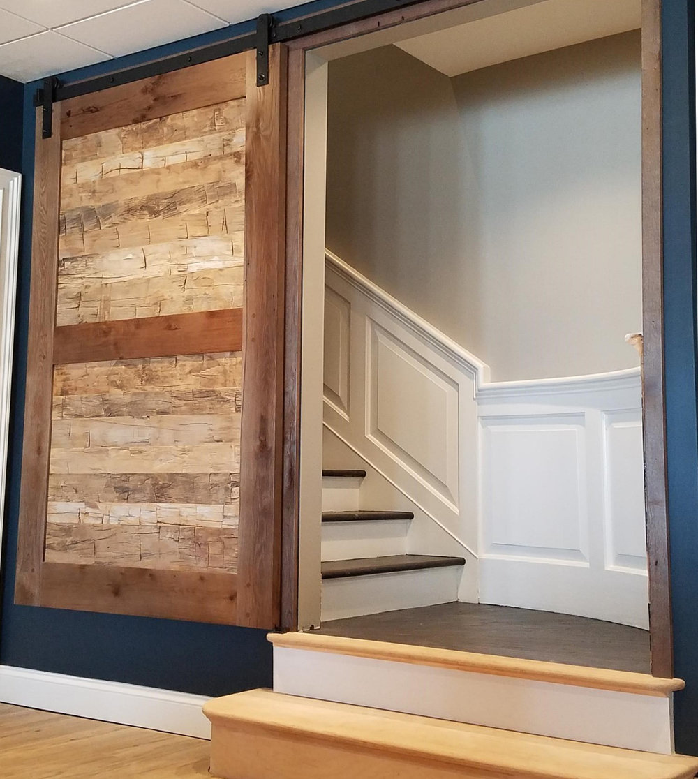 Reclaimed hand hewn timber skins were customized for the inset panels on this lower level rec room door.
