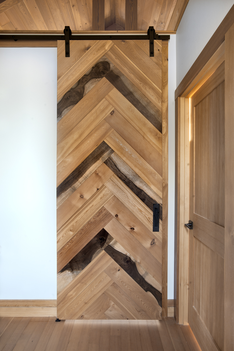 A mixture of walnut, larch, and Douglas fir scraps from a new home build in a herringbone pattern act as wall art and privacy to a master bedroom.