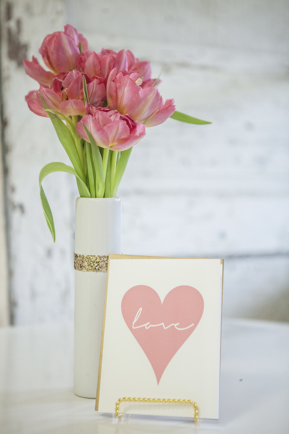 White Cylinder with Gilded Band- $30 Featuring a half dozen Tulips in Bold Pink. White cylinder vase is adorned with a gold gilded band. Includes your choice of greeting card. No upgrades are available for this item.