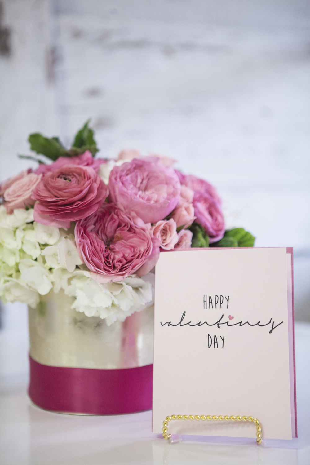 Gilded Cylinder with Fuchsia Band - $80 Featuring Garden Roses, Roses, Ranunculas, Hydrangea & Scented Geranium Leaves. Includes your choice of greeting card. Upgrade Available -$15 (Additional Ranunculas & Tulips)