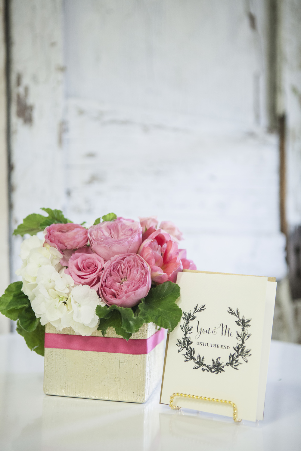 Gilded Cube with Bold Pink Band- $60 Featuring Garden Roses, Roses, Tulips, Ranunculas, Hydrangea & Scented Geranium Leaves. Includes your choice of greeting card. Upgrade Available -$10 (Additional Ranunculas & Tulips)