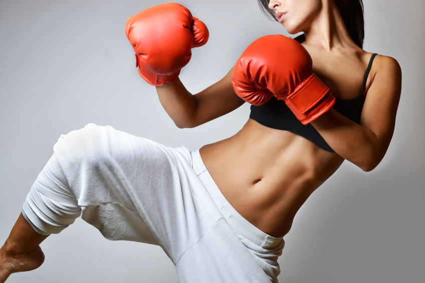 Young woman in kick boxing pose with boxing gloves on. Ultimate Health Personal Training Center - Hollywood