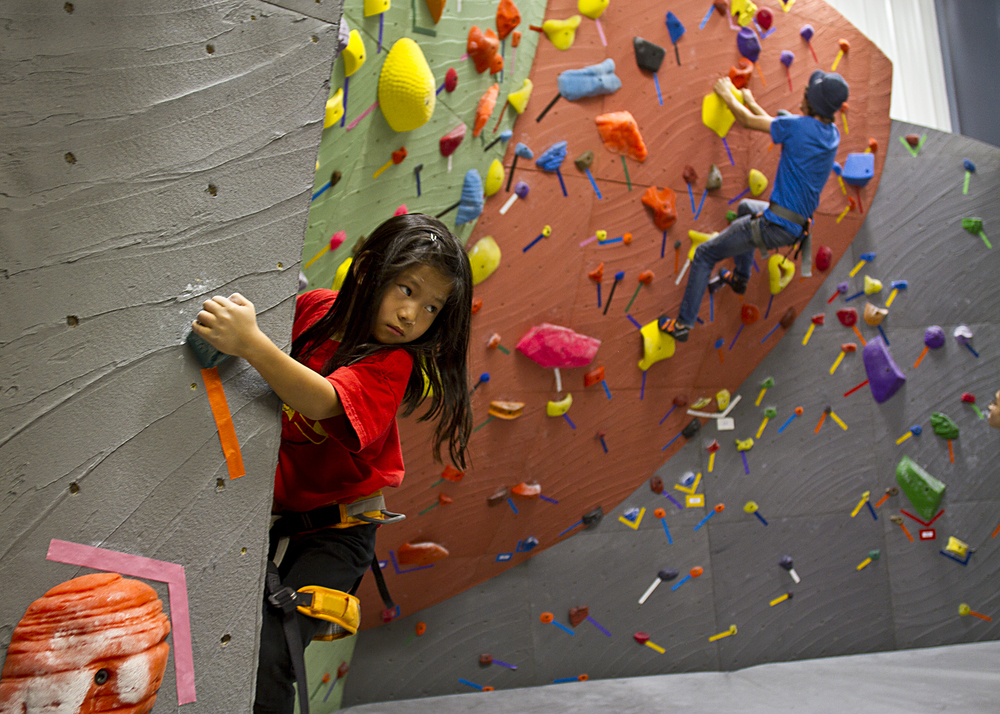 One young climber begins her ascent on one of the many climbing walls at Island Rock Gym shortly after the athletic facility's grand opening in late September 2013.