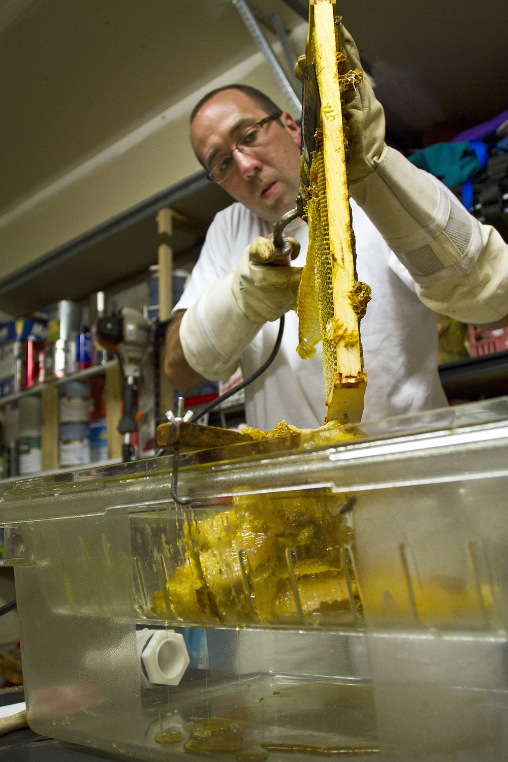 Allen Turnbull, a Bainbridge Island firefighter with two years of beekeeping experience, uncaps a frame of honey comb from one of his hives with a heated knife.