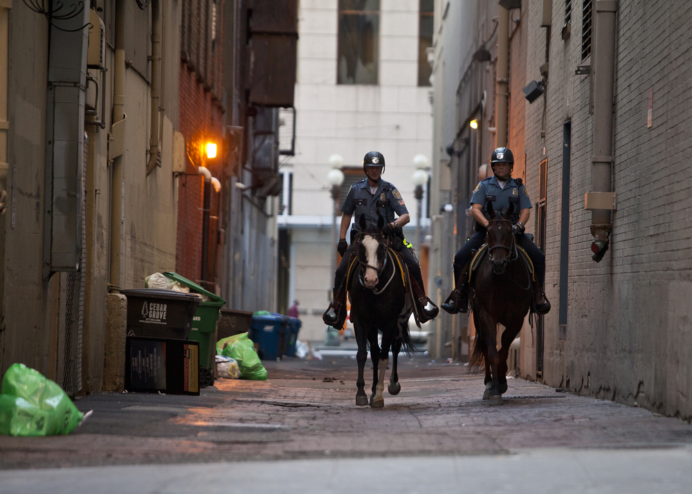 Two Seattle Police Officers patrol an alley near the established route for the 2014 Torchlight Parade.