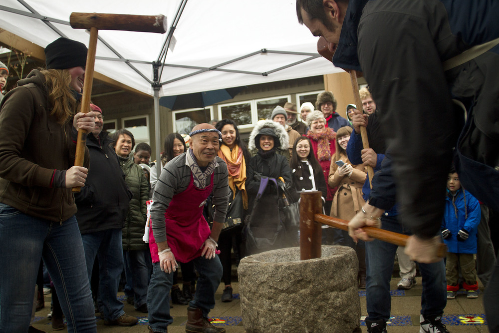 Shoichi Sugiyama, a volunteer with the Bainbridge Island Japanese American Community and staple figure at the island's annual New Year's mochi tsuki event, watches as the guests he instructed take their turn pounding the steamed rice with large wooden mallets.