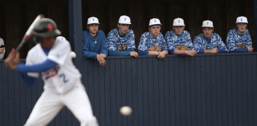 The Bainbridge Spartan dugout watches a Rainier Beach visitor at bat.