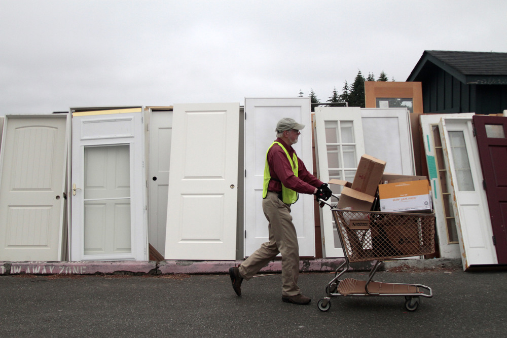 A volunteer at the 2016 Bainbridge Island Rotary auction and rummage sale - six acres of bikes, housewares, books, games, clothes, art, boats and more - walks past a line of doors while organizing the event's layout.