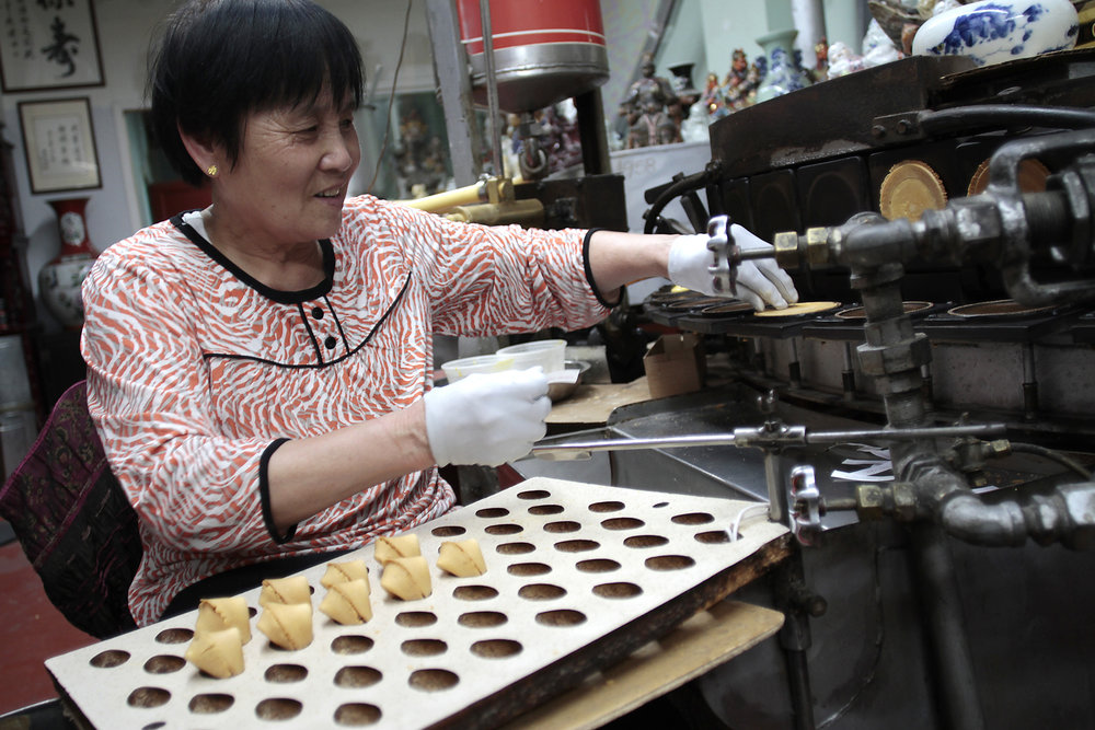A woman folds fresh fortune cookies into shape around the tiny pieces of paper at the famed Golden Gate Fortune Cookie Company in San Francisco, Sept. 2017.