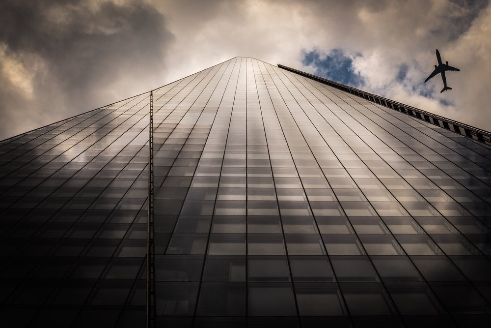 The Shard, London. The view looking up from below nicely finshed off with a plane.