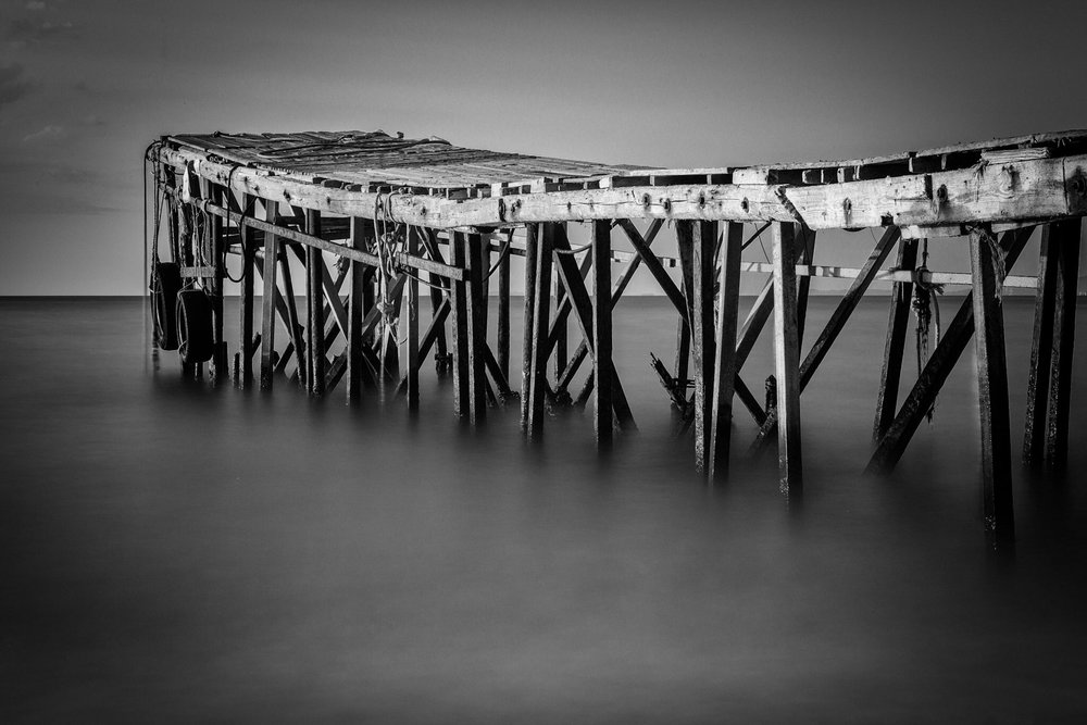 Black and white picture of the jetty on Nissaki Beach in Corfu